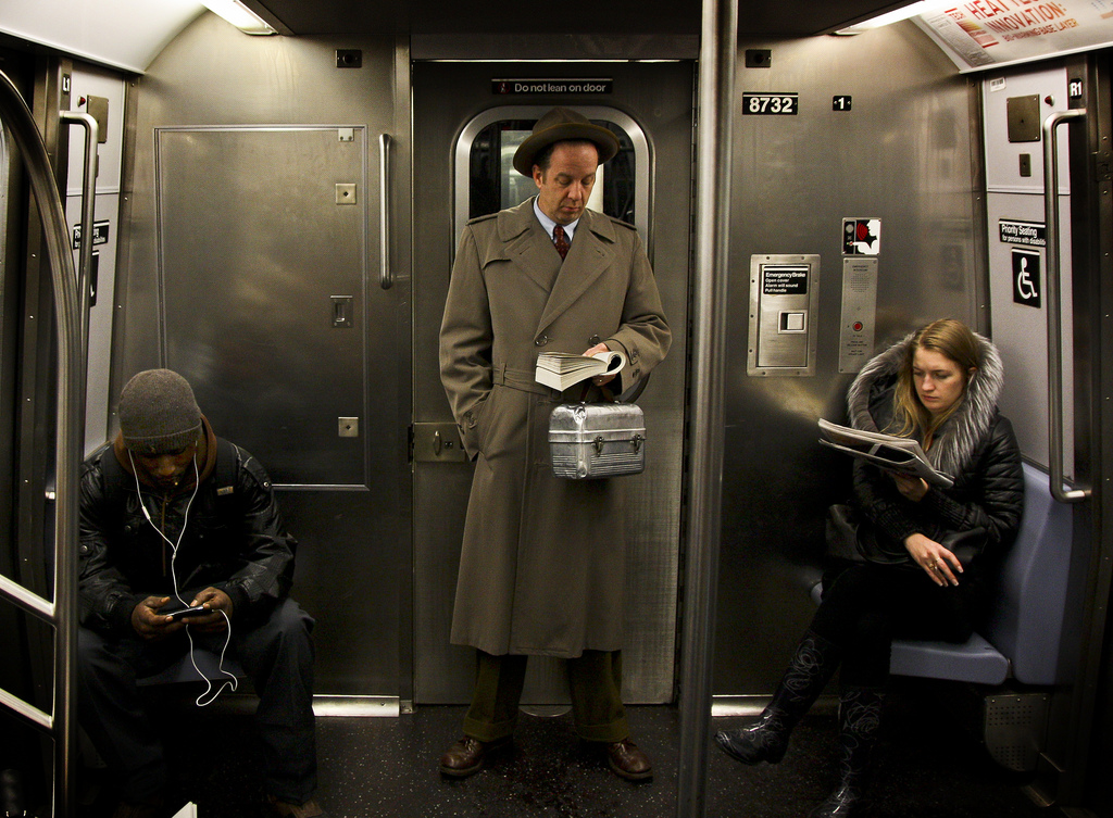 Three passengers occupy themselves as they ride a Q train into Brooklyn.