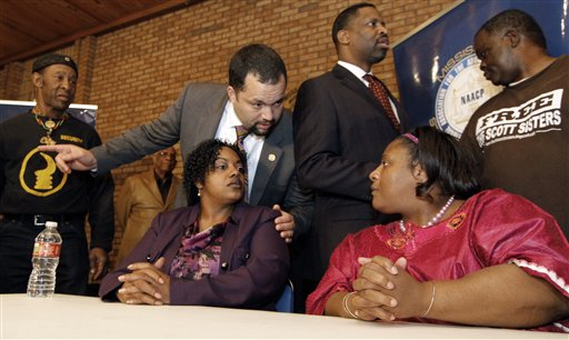 National Association for the Advancement of Colored People National President Ben Jealous, left, listens as Jamie Scott cries while speaking about she and her sister being released from a Mississippi prison after serving 16 years for armed robbery during a news conference in Jackson, Miss.