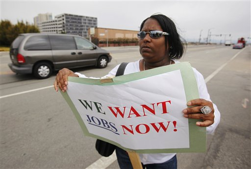 Unemployed Deanna Rice, who was released after five years in a federal prison, holds up sign looking for work in construction during a workers rally outside of a construction zone in San Francisco. (AP Photo/Paul Sakuma)