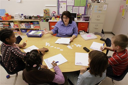 A Title I resource reading and math teacher, right, works with her third grade students. Title I, which provides grants for low-income schools. (AP Photo/Seth Perlman)
