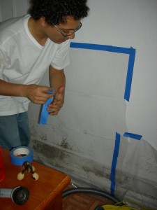 Ray Lopez temporarily sealing off visible mold using a simple plastic barrier.
