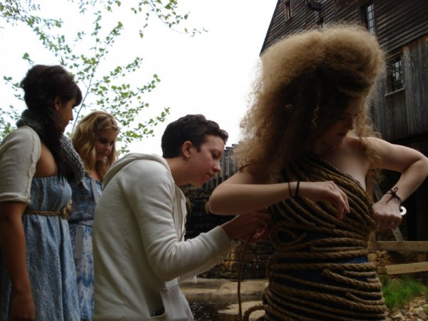 Designer Gennie Catastrophe adjusts a dress on a model during a photoshoot before the Art to Wear fashion show.