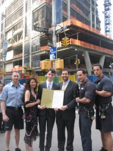 Brook Peters, Senator Squadron and Michelle Peters pose with firefighters at Ground Zero
