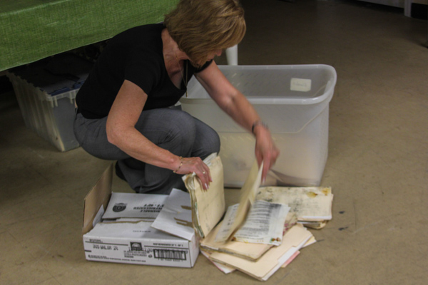 "Garson goes through a box of call sheets she just found that had been missing since Hurricane Sandy. The box is still filled with water from the storms flooding, and the papers have begun to mold. ""We're still picking up the pieces from the storm,"" she says."