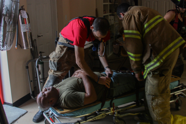 "Dave Ostrowski (l) and Aaron Hale (r) strap a neighborhood volunteer onto a stretcher during their drill, which recreated an explosion that left many people with critical leg and back injuries. ""Drilling keeps you an expert in your field,"" Garson said. ""We have always had a standard of high quality and we have to keep that up."""